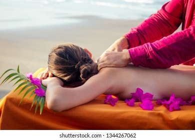 Ayurvedic relaxing massage ,health woman in spa salon getting massage the holiday beach.Beautiful girl enjoying day spa resort, lying down on the table treatment procedure.male master neck therapist