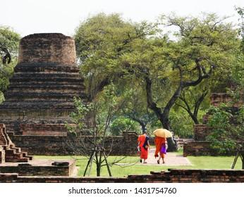 Ayuthaya, Thailand- February 26, 2019: Buddhist Monks tour the ancient ruins of Wat Phra Ram.