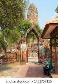 Ayuthaya, Thailand- February 26, 2019: Tourists photograph the ancient Prang at ruined Wat Phra Ram while attendants sit by the gate.