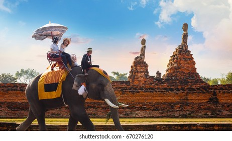 AYUTHAYA, THAILAND - NOVEMBER 4 2016: Unidentified Asian tourists with an elephant at  Wat Chaiwatthanaram temple in Ayuthaya Historical Park, a UNESCO world heritage site