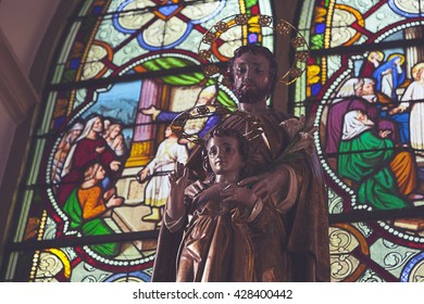 AYUTHAYAI, THAILAND - MAY 6 : St. Joseph Apostle and baby Jesus with stained glass window in the background in St. Joseph Church in Ayuthaya, Thailand on May 6,2016.