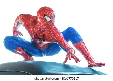 Ayuttaya, Thailand - November 16, 2015 : Spider-Man model sit down on the car isolated on white background.
