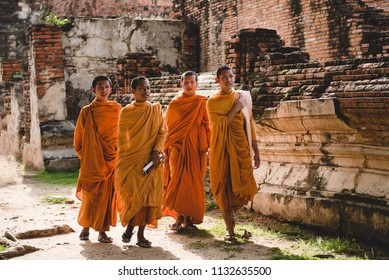 Ayutthaya, Phra Nakhon Si Ayutthaya/ Thailand - August 26, 2017: Monks, group of young friends walking trough historical city. Old town made of bricks, which are ruins now, named Ayutthaya.