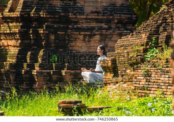 AYUTTHAYA, THAILAND - 26 OCT 2017 -  Woman meditate to respect Buddha at World  Heritage Temple in Ayuthaya