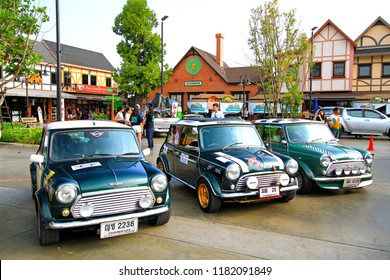 Ayutthaya, Thailand - December 16, 2017: Three classic green Mini Austin cooper parked in Mini Mountain 4.0 festival with people and Vintage home background - Transportation, Vehicle and Vintage car