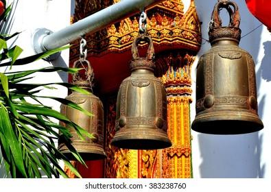 Ayutthaya, Thailand - December 22, 2010:   Three ornamental bronze bells hang from a metal pole at the Ubosot sanctuary hall at Wat Prayathikaran