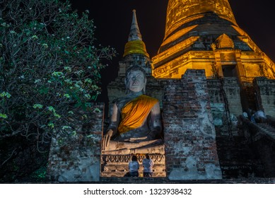 Ayutthaya ,Thailand - february 19, 2019 : Buddhists people (motion blur) with lighted candles in ancient temple on Magha Puja day at Ayutthaya province of Thailand.