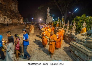 Ayutthaya ,Thailand - february 19, 2019 : Buddhists people walking (motion blur)  with lighted candles in hand around a ancient temple on Magha Puja day at Ayutthaya province of Thailand.