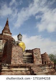 AYUTTHAYA, THAILAND - JUNE 6, 2020: Ancient Pagoda and Buddha Statue at Wat Yai Chai Mongkhon.