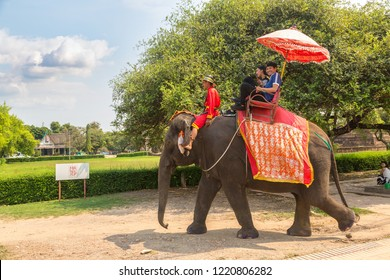 AYUTTHAYA, THAILAND - MARCH 22, 2018: Tourists riding on an elephant in the ancient city Ayutthaya, Thailand in a summer day