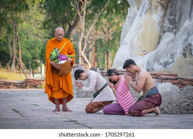 Ayutthaya, Thailand - March 8, 2020 : Young buddhist people is making merit with monk at temple of the reclining buddha (Wat Lokayasutharam) in Ayutthaya Province,Thailand.