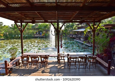 AYUTTHAYA, THAILAND - MAY 16, 2018 : the fountain in the center of the pond are spouting to the sky in front of restaurant outdoor table under afternoon sun light