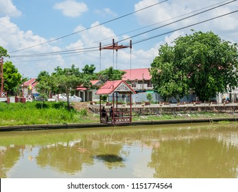 Ayutthaya, Thailand - May 23, 2018: People crossing the canal after visiting Wat Niwet Thammaprawat, Thai Buddhist temple, in Bang Pa-In, Ayutthaya, Thailand.