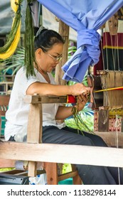 AYUTTHAYA , THAILAND - Nov 24, 2013: Female worker behind the machine. Fabricates beautiful tapestries.Thailand.