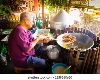 """Ayutthaya, Thailand - November 11, 2018 : The old chef is frying Thai  old dessert called """"Khao Moa Tod"""", Battered and Deep-Fried Unripe Rice and Grated Coconut Banana Rolls, in the big pan."""