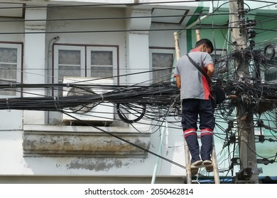 Ayutthaya Thailand-September 30,2021: Technician man standing on ladder without safety belt while repairing internet cables. Risk and unsafe work. Buildings background.