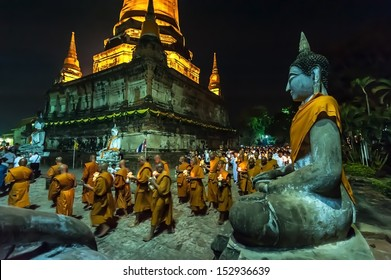 AYUTTHAYA,THAILAND-MAY 24:Visakha Bucha Day,Buddhist monk and people walk with lighted candles in hand around a temple to the Buddha on May 24, 2013 in ,Watyaichimongkol temple,Ayutthaya,Thailand.