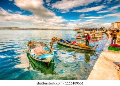 Ayvalik, Turkey - February 14, 2014 : Fisherman is selling fresh fish in old harbour.. Ayvalik is populer tourist destination in Turkey.