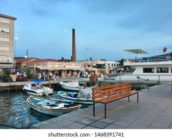 AYVALIK, TURKEY - JULY 12, 2019: Fishing boats and Ayvalik city center background landscape in old touristic town Ayvalik.It is a small city in the northwestern Aegean Sea off the coast of Balikesir.