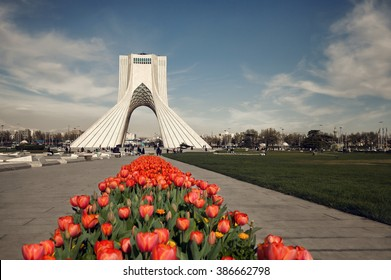Azadi monument behind a row of red tulips in Tehran on springtime, edited with brown vintage filter.
