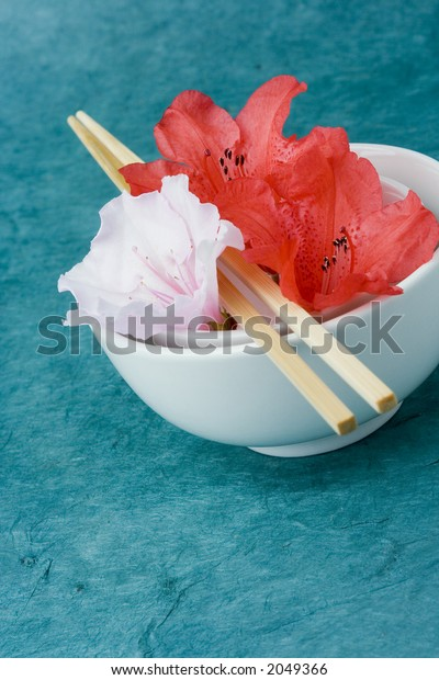 Azaleas or Rhododendron flowers positioned in two rice bowls with chop sticks. Conceptual representation of presentation, styling, food and freshness.