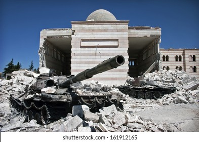 AZAZ, SYRIA - AUGUST 21, 2012 - A destroyed tank in front of a similarly ruined mosque.
