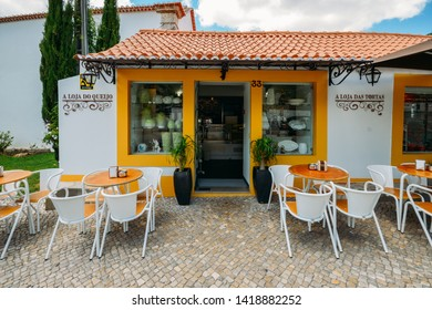 Azeitao, Portugal - June 7, 2019: Shopfront selling local products such as cake, cheese and wine built in traditional Portuguese architecture in the village of Azeitao, Portugal