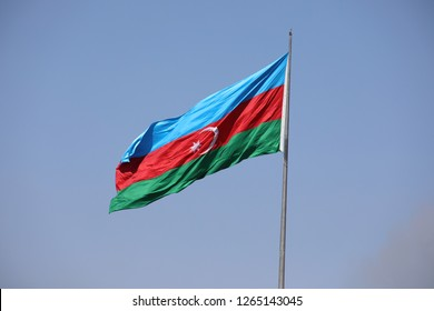Azerbaijan flag in Baku, Azerbaijan. National sign background. Red Green Blue flag. Azerbaijan national flag with Crescent moon. Flags waving wind