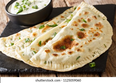 Azerbaijan flat bread qutab with greens close-up on the table. horizontal
