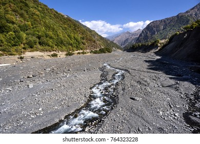 Azerbaijan, Greater Caucasus, near Qabala, Durja and Laza: Huge rocky river bed with streams, floating water and mountain chain - scenery