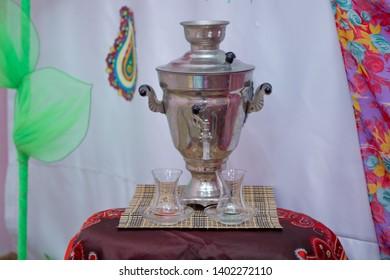 Azerbaijan  tea samovar Concept traditional Azerbaijan culture object samovar .Crystal glass of tea on with metal samovar .
