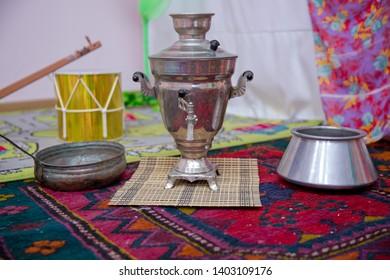 Azerbaijan  tea samovar Concept traditional Azerbaijan culture object samovar .Crystal glass of tea on with metal samovar . cast iron old pot . Iron Wok very old