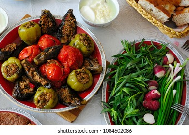 Azerbaijani dolma with eggplant, tomato and pepper, yogurt, greenery and bread on the table