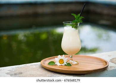 Azerbaijani and Turkish ayran - cold greek yoghurt drink - on wooden bamboo tray with straw and spoon and daisy flower in the garden by the green pool