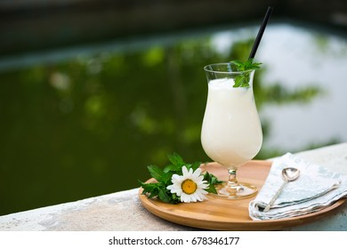 Azerbaijani and Turkish ayran - cold greek yoghurt drink in cocktail glass with straw, spoon, fresh mint leaves and daisy flower by side on bamboo tray with pool background