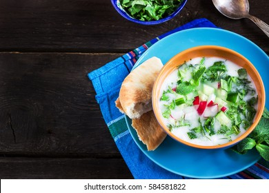 Azerbaijani/russian cold soup with greens on dark rustic background. Top view. Selective focus.
