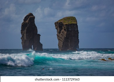 Azores, Atlantic ocean, San Miguel island coast with rough ocean with blue green splashing waves two cliff rocks in water  and cloudy sky on background