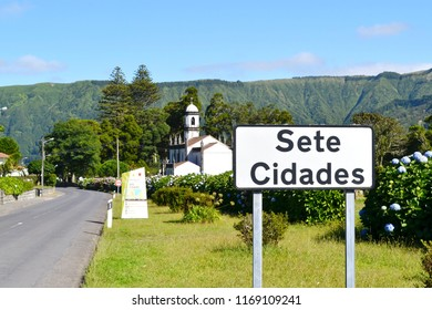 AZORES, PORTUGAL - SEPTEMBER 27, 2016: Town sign for Sete Cidades, a civil parish on Sao Miguel Island, with Saint Nicolas Church in the background
