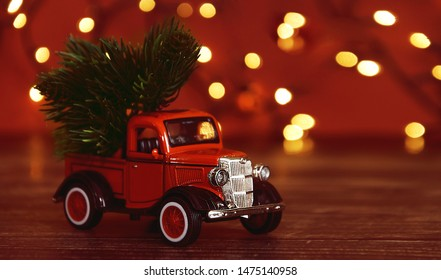 Azov, Russia, 31-July 2019. Red car carrying a Christmas fir tree on the snow background. Concept for Merry Christmas and Winter holidays.Copy space.