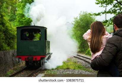 AZPEITIA, SPAIN - AVRIL 28, 2018: Steam train arrival. Attraction for kids and parents. Azpeitia, Spain. Father holding daughter closing ears because of noisy locomotive whistle. Selective focus.