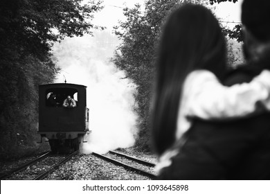 AZPEITIA, SPAIN - AVRIL 28, 2018: Steam train arrival. Attraction for kids and parents. Azpeitia, Spain. Father holding daughter closing ears because of noisy locomotive whistle. Selective focus. Bla