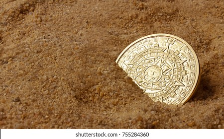 Aztec coin laying in sand side view.