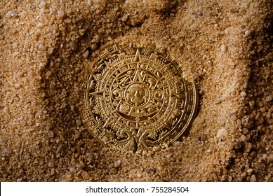 Aztec coin laying in sand upper view.