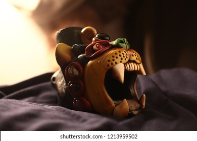 An Aztec jaguar warriors whistle on a cloth, natural light tones.