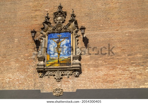 Azulejo showing Jesus on the cross on an external wall of the Church of the Annunciation (Iglesia de la Anunciacion) in Seville Spain. The church in Renaissance style was built in 1565