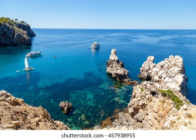 Azure bay with crystal clear water, which offers incredible views of the vast expanses. Lonely sailer rock on the waves and go into the distance cruise liners. Mallorca. Spain