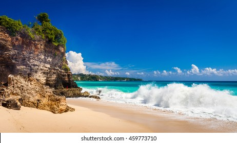 Azure beach with rocky mountains and clear water of Indian ocean at sunny day / A view of a cliff in Bali Indonesia / Bali, Indonesia