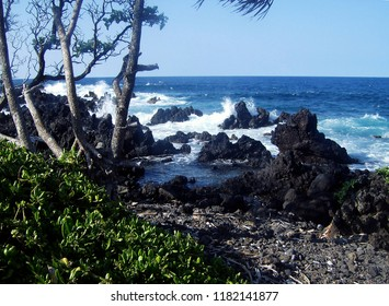 Azure blue ocean waves crashing against lava rocks on a beach in Hawaii.