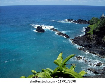 Azure blue ocean waves crashing against lava rocks on the Hawaiian coastline.  A tropical paradise.