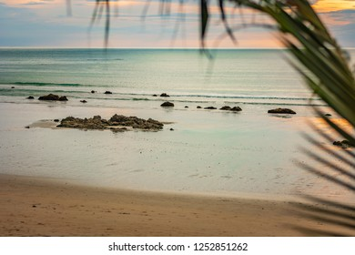 The azure coast, the beach on the island of Thailand, the sunset, the rocks by the shore and the blurred palm tree as a natural border of the landscape, Thailand